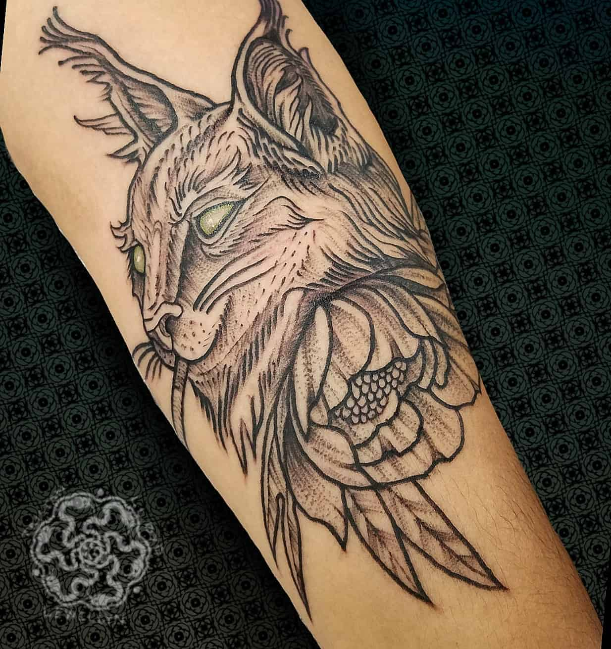 blackwork tattoo of a cat and flower on a forearm