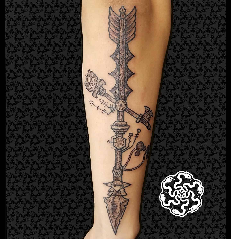 blackwork tattoo of an arrow