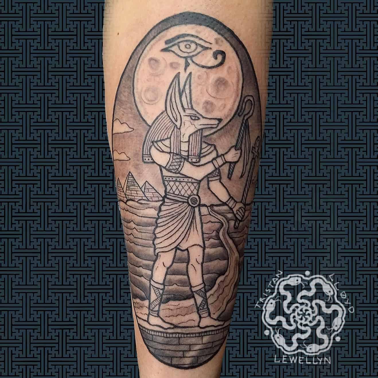 blackwork tattoo of egyptian annubis on a forearm