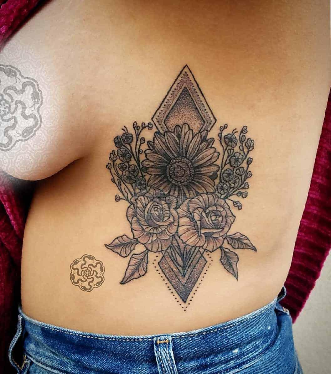 blackwork tattoo of floral arrangement on ribs