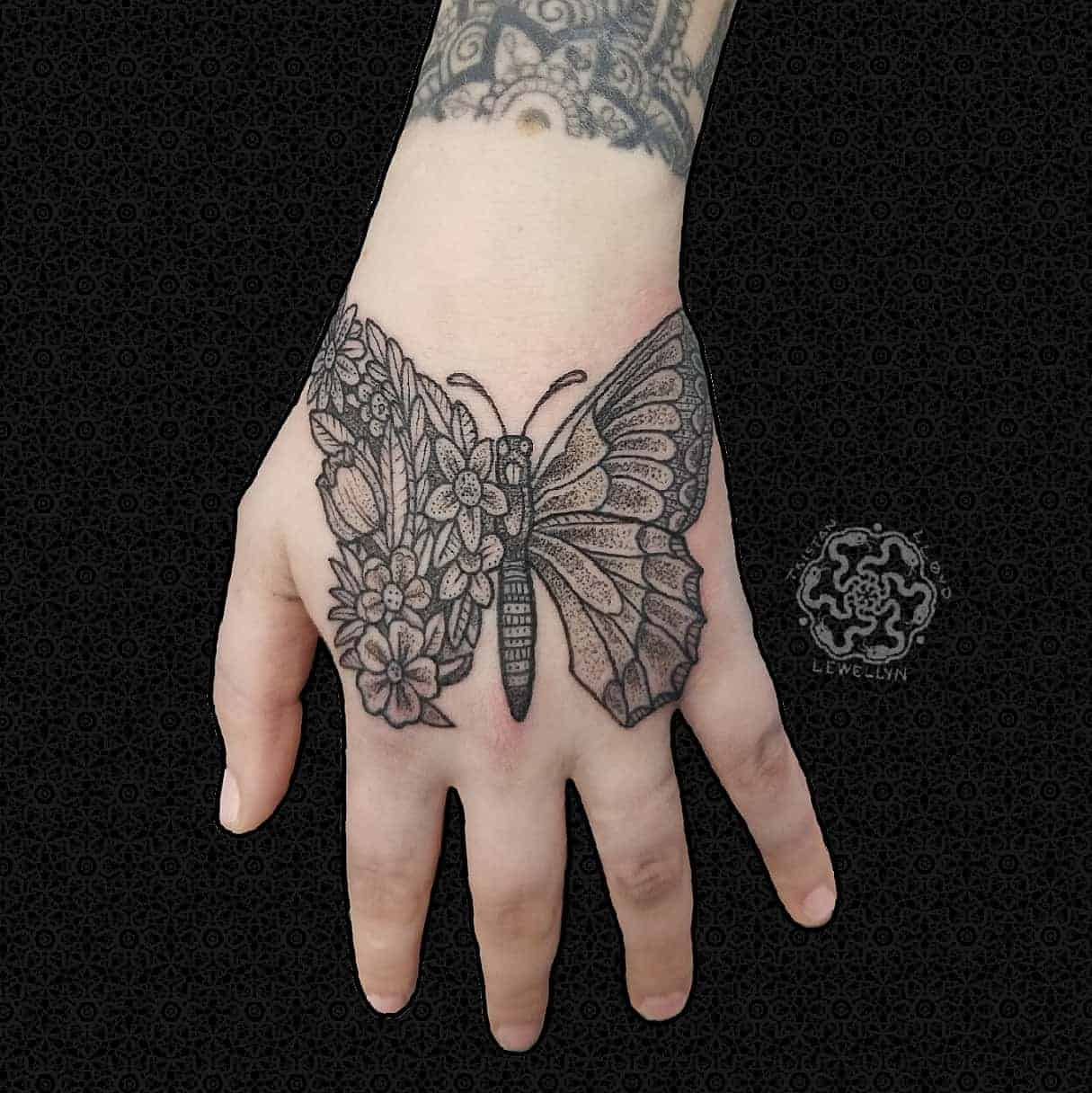 blackwork tattoo of floral butterfly on a hand