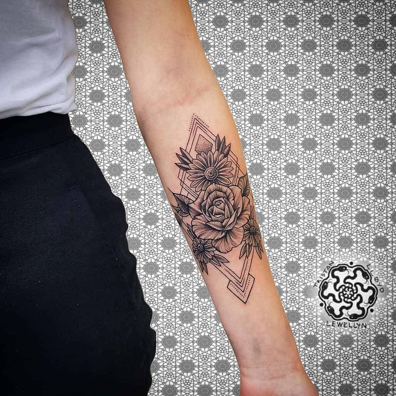 blackwork tattoo of geometric flower arrangement on forearm