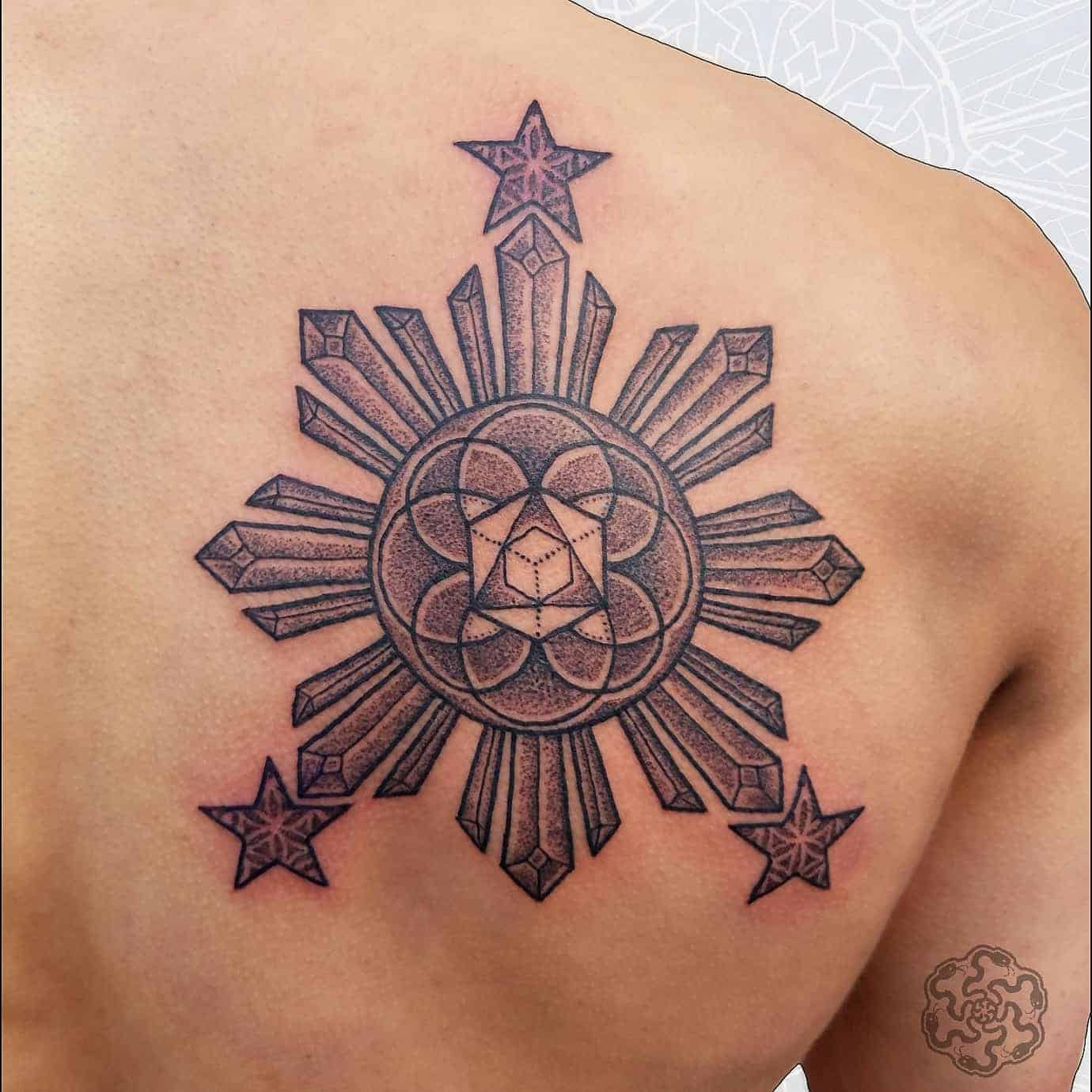 blackwork tattoo of geometric philippino sun on a shoulder