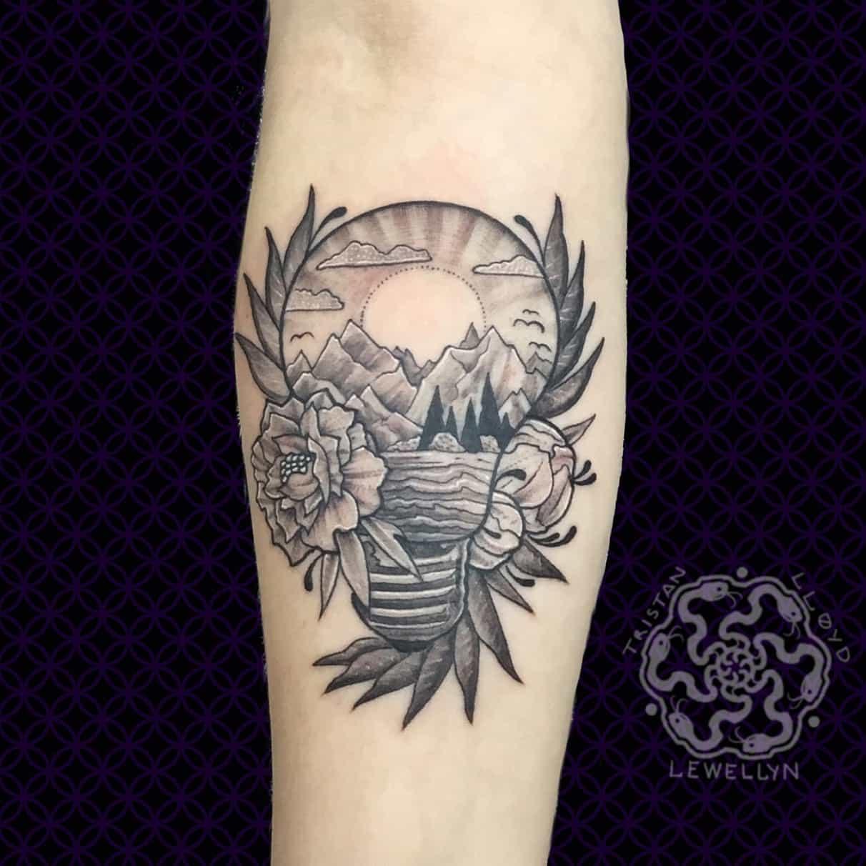 blackwork tattoo of landscape and lighthouse