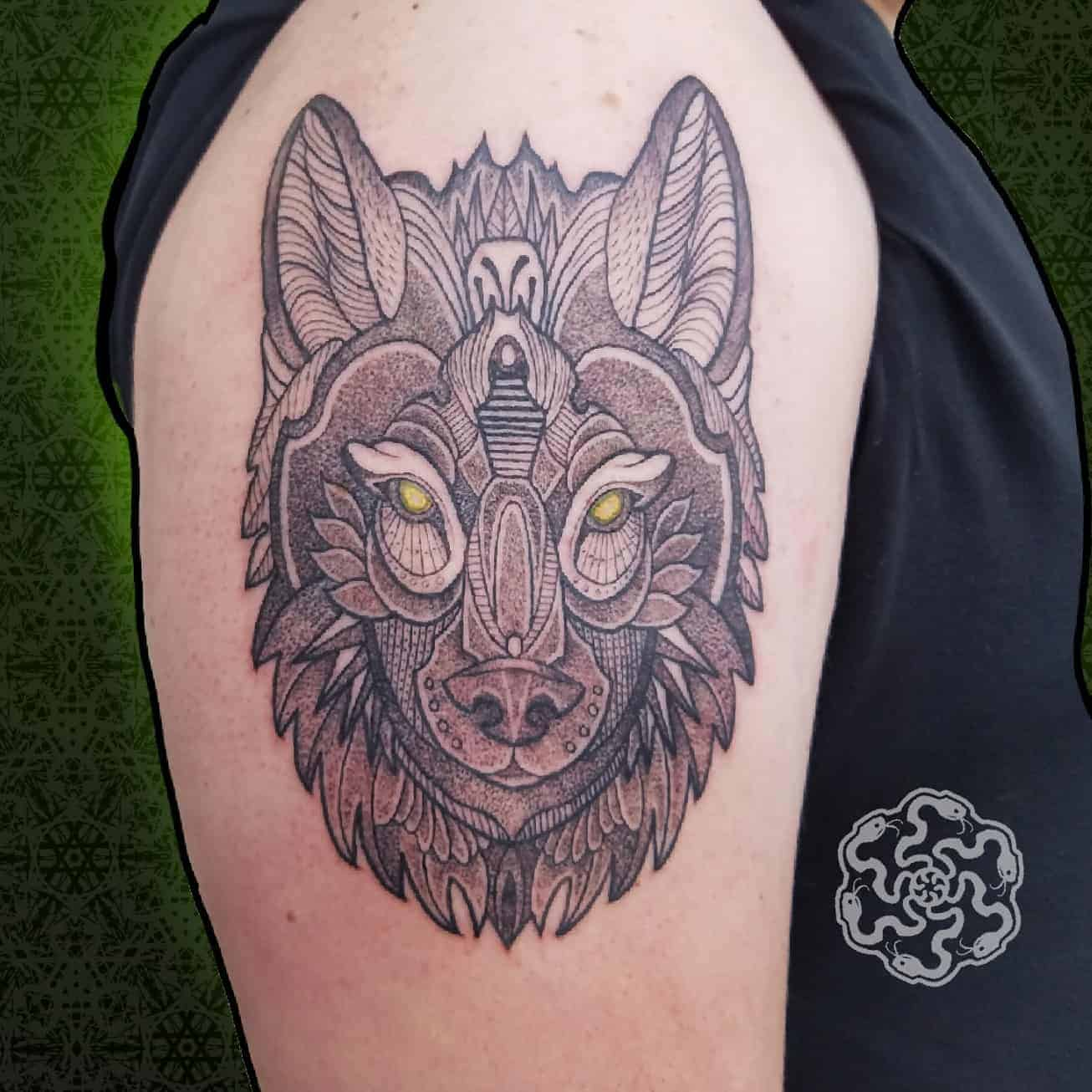 blackwork tattoo of manadala wolf on an upper arm