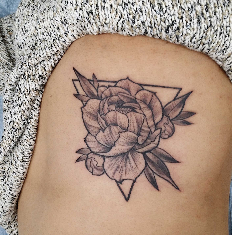 flower-tattoo-of-peony-on-ribcage-in-blackwork-tattoo-style