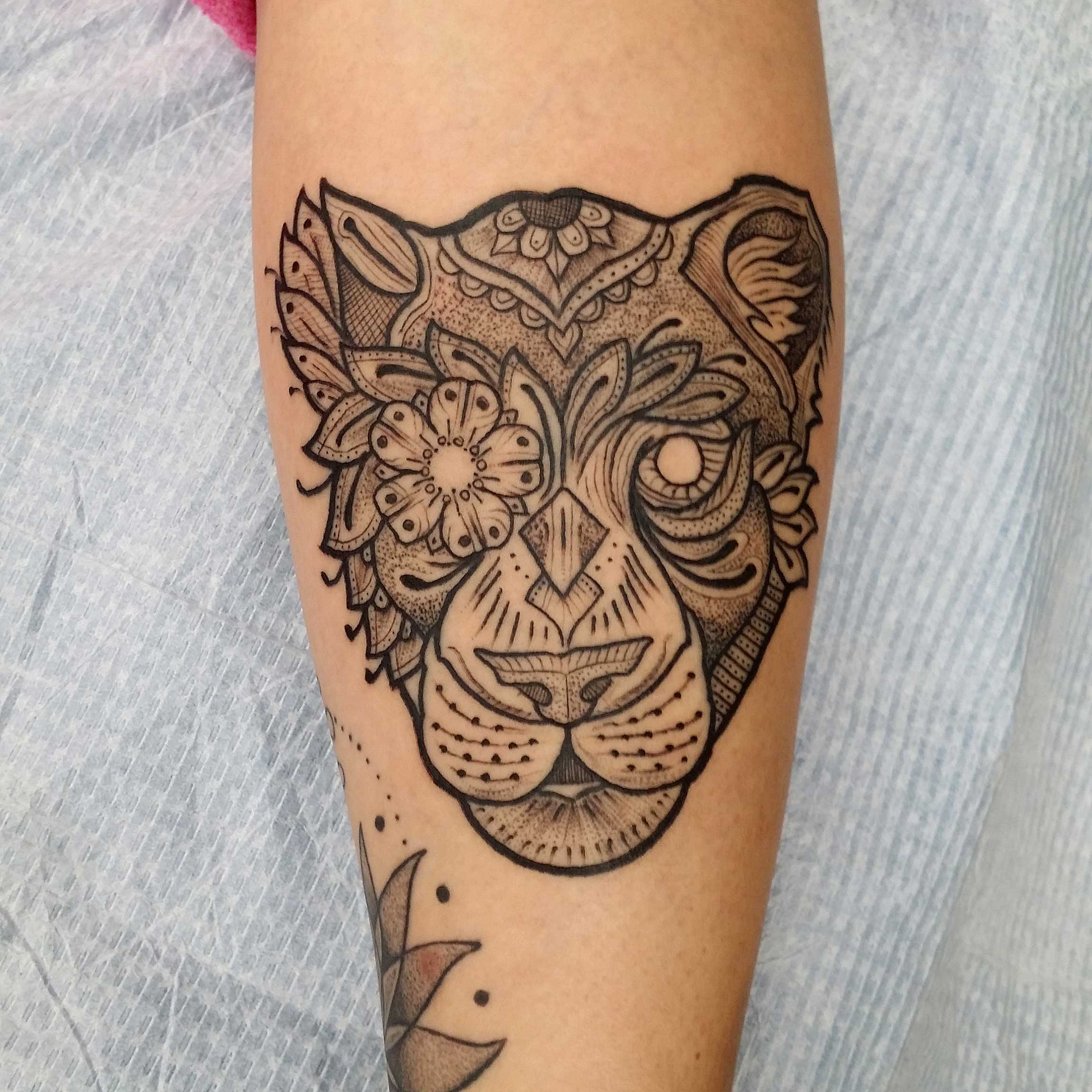 geometric-style-tattoo-in-all-black-of-lioness