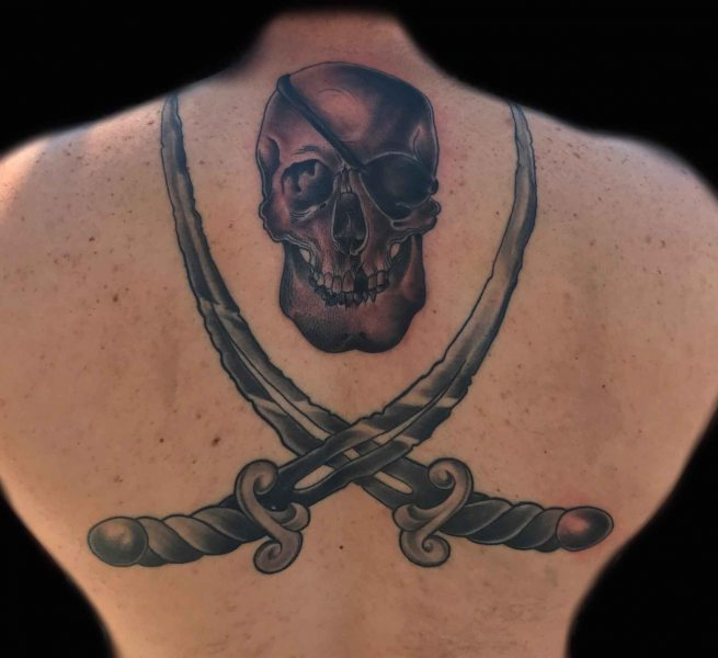 black-and-gray-tattoo-of-skull-snd-swords-by-Roger-Solis